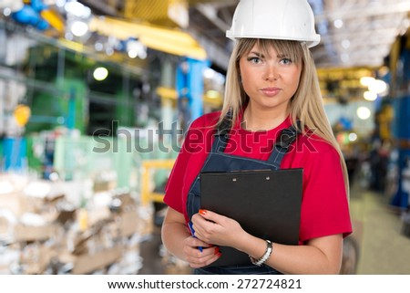 Industrial caucasian female inspector worker with clipboard at factory workshop background - stock photo