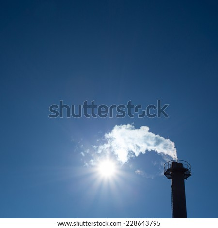 industrial chimney exhausting steam in blue sky  - stock photo