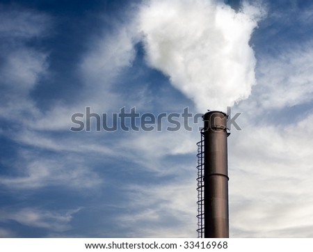 Industrial chimney smoking over blue sky with clouds