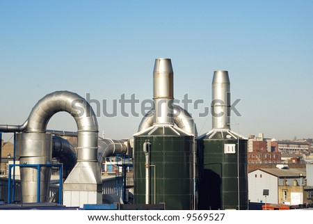 Industrial chimneys and storage tanks with buildings in the background.