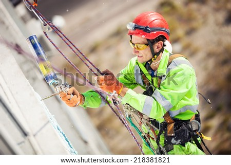 Industrial climber on a building during winterization works - stock photo