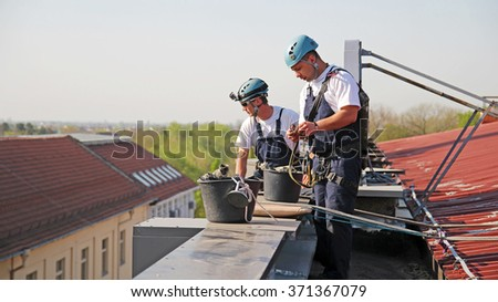 Industrial Climbers Preparing for Climbing. Window and Facade Cleaning.  Climbers checking climbing gear. Glass Cleaning Services.  - stock photo