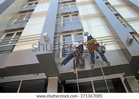Industrial Climbers Washing Facade of a Modern Building. Window and Facade Cleaning. Glass Cleaning Services. - stock photo