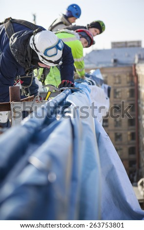 Industrial climbers working on a roof of a building - placing an advertising banner - stock photo
