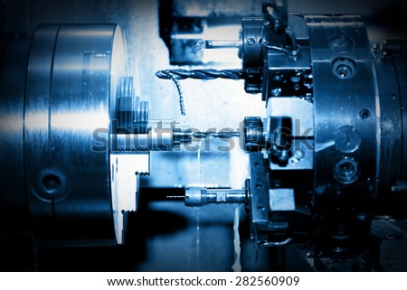 Industrial CNC drilling and boring machine at work close-up. Industry concept, blue tone. - stock photo