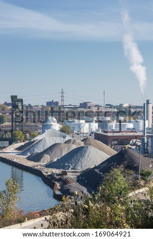 Industrial Complex:  Large piles of aggregate materials and a tank farm along the bank of the Cuyahoga River in Cleveland, Ohio