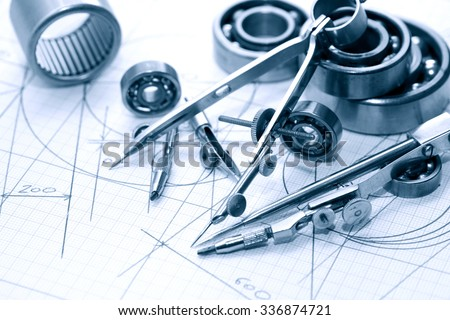Industrial concept. Drawing instrument near ball bearing on graph paper background - stock photo