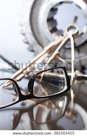 Industrial concept. Spectacles near divider and gear on glass surface against gray background