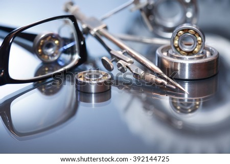 Industrial concept. Spectacles near divider and gear on glass surface against gray background - stock photo