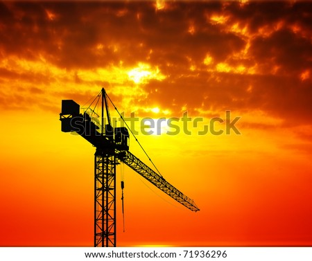 Industrial construction crane at sunset - stock photo