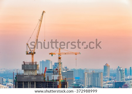 Industrial construction crane during sunset in Bangkok city. - stock photo