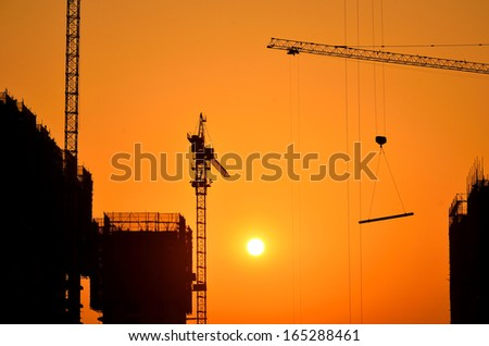 Industrial construction cranes and building at sunset   - stock photo