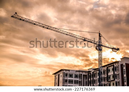 Industrial construction cranes and building silhouettes on sunrise.  - stock photo