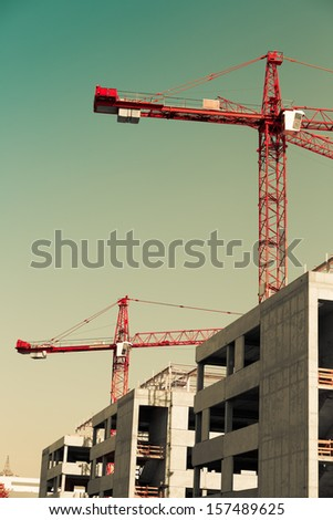 Industrial construction cranes and building silhouettes over - stock photo