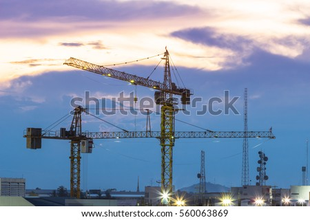 Industrial construction cranes and building silhouettes over amazing sunset sky abstract background in the evening