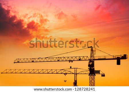 Industrial construction cranes and building silhouettes over sun at sunrise - stock photo