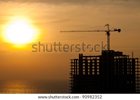 Industrial construction cranes and building silhouettes with  sunrise - stock photo