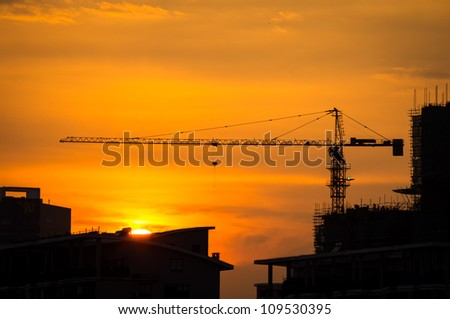 Industrial construction cranes and building silhouettes with sunset - stock photo