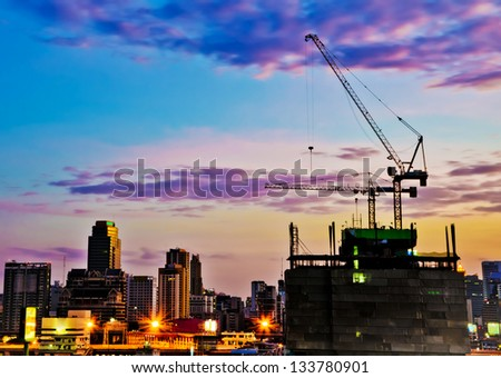 Industrial construction cranes and city  at sunrise. - stock photo