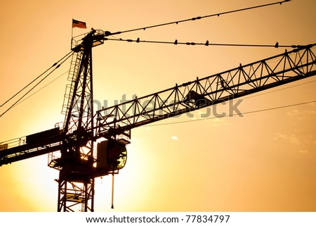 Industrial construction cranes over sun at sunset. - stock photo
