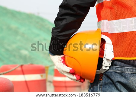 Industrial construction safety work concept of man worker holding hardhat on location site - stock photo