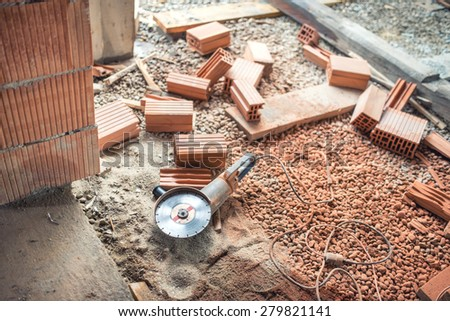 Industrial construction site tools, angle grinder used for cutting bricks at building renovation, reconstruction - stock photo