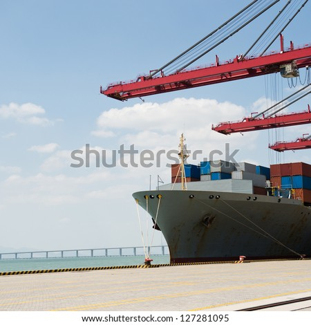 Industrial container cargo freight ship with working crane bridge. - stock photo