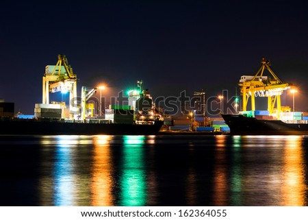 Industrial Container Cargo freight ship with working crane bridge in shipyard