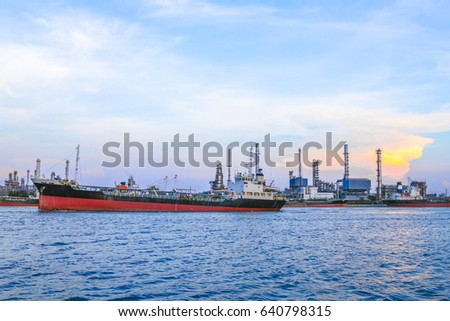 Industrial Container Cargo freight ship with working crane bridge in shipyard at dusk for Logistic Import Export with evening sky background