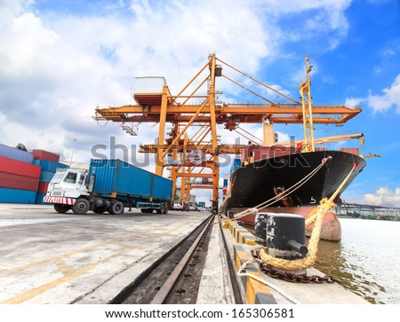 Industrial Container Cargo freight ship with working crane bridge in shipyard with truck - stock photo