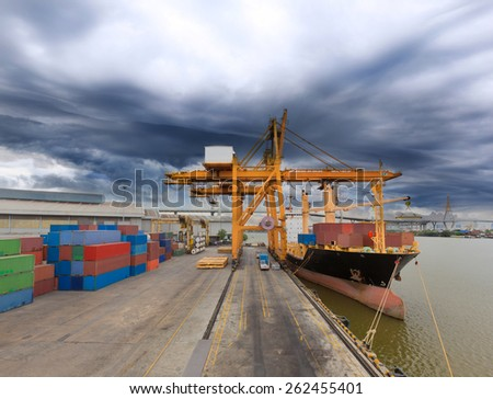 Industrial Container Cargo freight ship with working crane bridge in shipyard with Weather Strom is Coming - stock photo