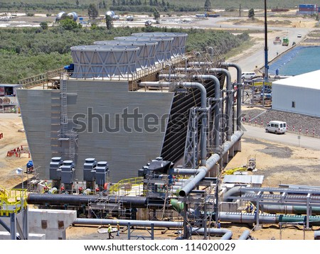 Industrial cooling tower, pipes and pumps - stock photo