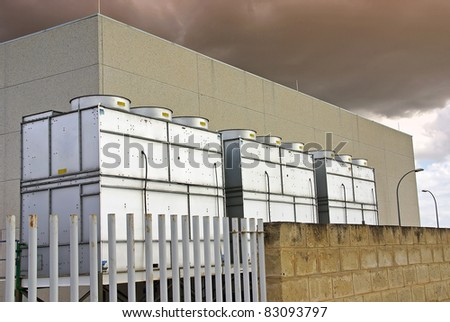 Industrial Cooling Towers used for refrigeration purposes in a big building - stock photo