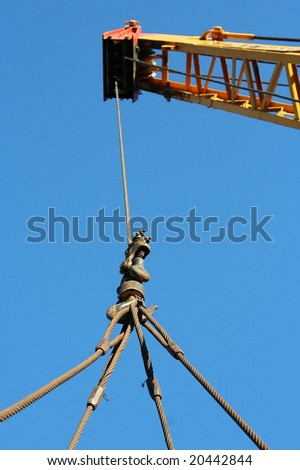 Industrial crane boom hoisting up a suspended load by cables - stock photo