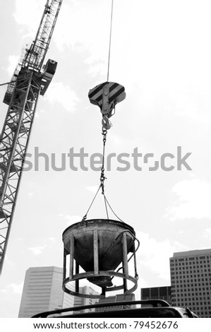 industrial crane hoisting concrete mixing container in inner city with urban infrastructure skyscrapers in the background - stock photo