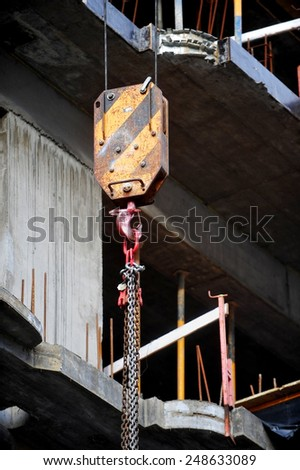 Industrial crane hook on a construction site - stock photo