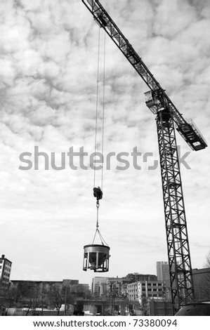 industrial crane lifting cement mixing container  above a city background. - stock photo
