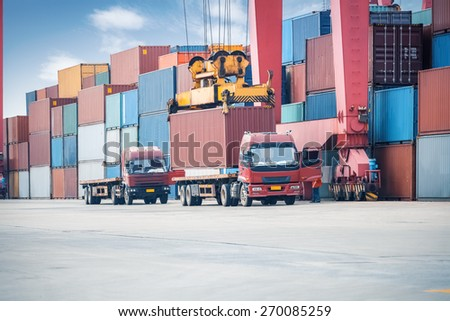 industrial crane loading containers in a cargo freight truck - stock photo