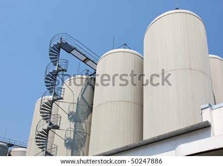 Industrial distillating columns in factory site with spiral stairs