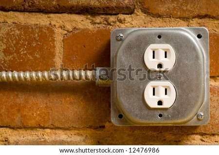 Industrial electrical outlet on a red brick wall, concept of power or connectivity etc. - stock photo