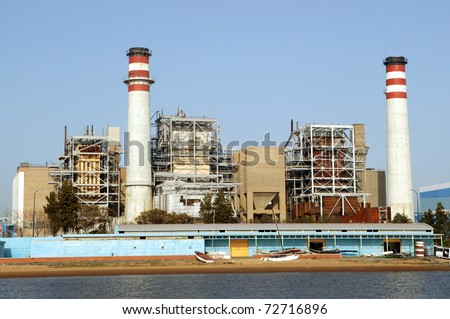 Industrial electrical power plant at the edge of a river - stock photo