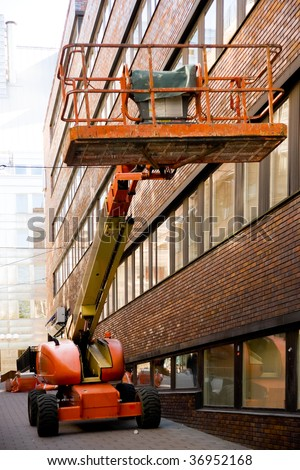 Industrial elevated crane platform in front of an office building - stock photo