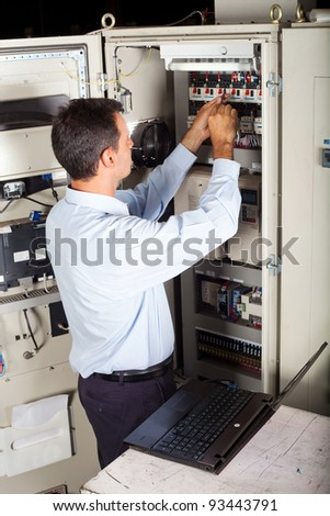 industrial engineer repairing computerized industrial machine - stock photo