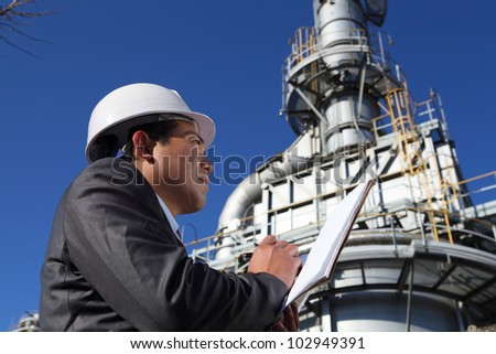 Industrial engineer standing in front of a large oil refinery machine, writing  under  pipes and cooling towers