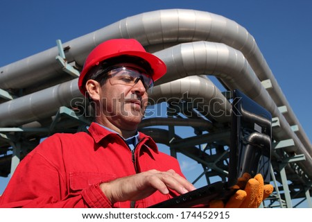 Industrial Engineer Working on a Notebook Computer Outdoor.Industrial engineer inside oil and gas refinery using notebook. - stock photo