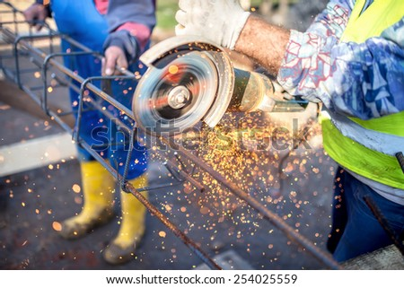 industrial engineer working on cutting a metal and steel bar with angle grinder, construction site details - stock photo