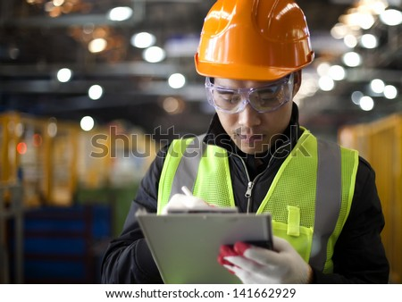 industrial engineer writing on notepad in factory - stock photo