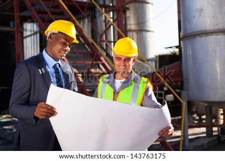 industrial engineers standing in front of a large oil refinery machinery with blueprint on hand - stock photo