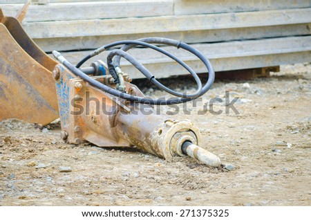 Industrial excavator jackhammer or drill unused on the dirty ground on a construction site in a close look with the cables and oil dripping out - stock photo