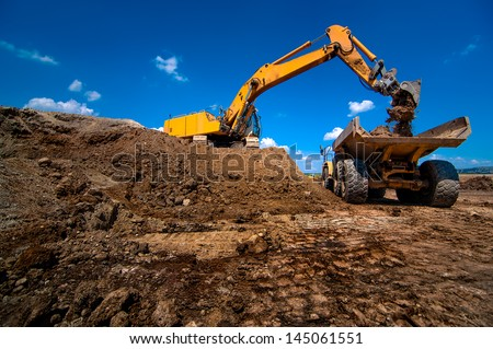 Industrial excavator loading soil material from highway construction site into a dumper truck - stock photo